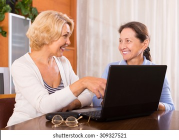 Two positive female pensioners sitting with laptop indoor. Focus on blonde