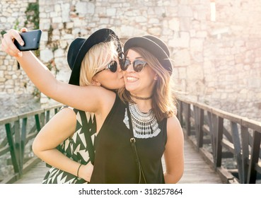 Two positive girls doing selfie with happy faces,selective focus