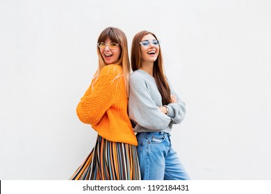 Two positive girls standing back to back on white background. Friendship concept. Wearing stylish outfit. Similar sunglasses.