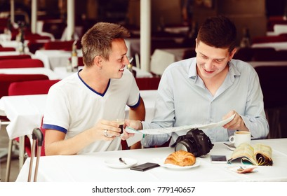 two positive men sitting with coffee and looking at map at a table in cafe