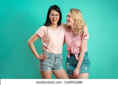 Two positive multiethnic young girlfriends hagging and having fun while shooting at studio over blue background with copyspace. Woman Apparel, Garments Clothing