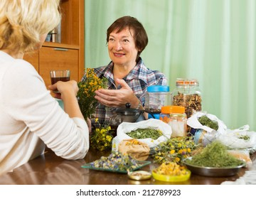 Two positive pensioner sitting at the table with herbal tea and herbs