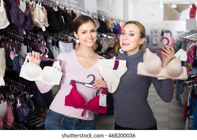 d923d4415 two positive russian female customers holding bras and panties in hands in underwear  store
