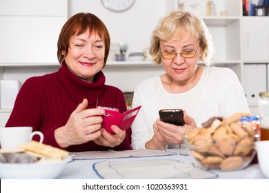 Two positive senior women using phones together over cup of tea