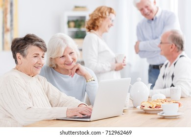 Two positive senior women using laptop, surfing the internet at nursing home with company of elderly friends talking in the blurred background