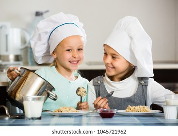 Two positive small girls eating healthy oatmeal in kitchen