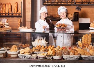 Two positive women selling bread and different pastry in bakery