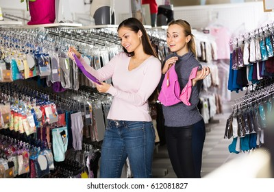 Two positive women together choosing panties in lingerie shop