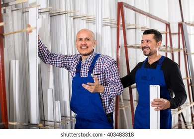 Two positive workmen in blue coverall with PVC windows and doors profiles at workshop. Selective focus