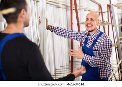 Two positive workmen in blue coverall in workshop of PVC windows and doors