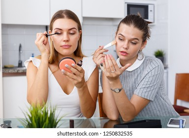 Two positive young female friend doing make up  at table with cosmetics in kitchen