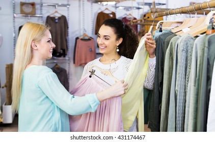 Two positive young girls choosing new clothes in shopping center. Focus on brunette
