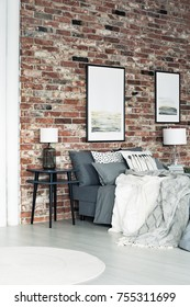 Two posters hanging on a brick wall in loft style bedroom with lamp on bedside table