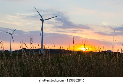 Two power generators behind a field of wheat on a summer evening in the Netherlands