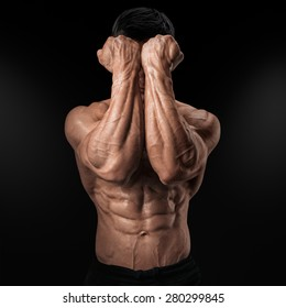 Two Power Mans Hands in Front of Face. Close-up of a man's fists and abs. Strong man's arm with muscles and veins.