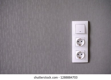 Two power sockets and Light switch on gray wall. Close-up.