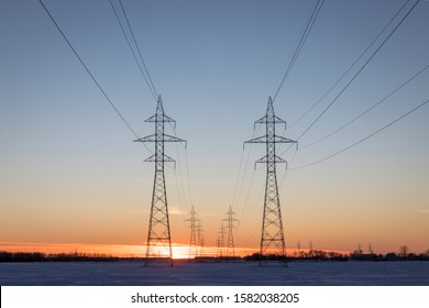 Two Power Transmission Towers Against a Prairie Sunset