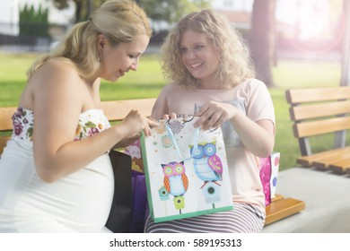 Two pregnant  women with shopping bags