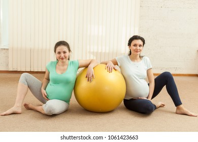 Two pregnant women are sitting near the ball