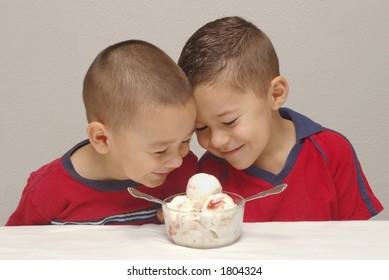 Two preschool brothers prepare to enjoy a large bowl of strawberry-cheesecake  ice cream