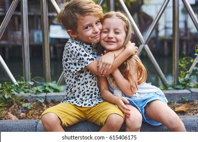 Two preschool children boy and girl sit together at the outdoor in the city in relation