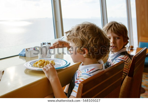 Two preschool kids boys eats pasta noodles sitting in school or nursery canteen. Happy children, twins, eating healthy organic and vegan food in restaurant. Childhood, health concept