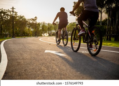 Two preson ride on bike on the road. Sport and active life concept sunset time. Couple of men riding on bicycle in a park. Blue sky with orange sun beam over the body of cyclist.
