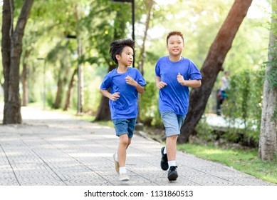 Two preteen Asian boy running in a public park with a lot of tree during summer.