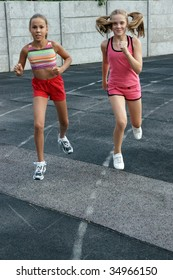Two preteen girls running on track