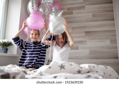 Two preteen sisters twins celebrate birthday day at the morning, active kids dressed in pajamas have fun in the bed with balloons