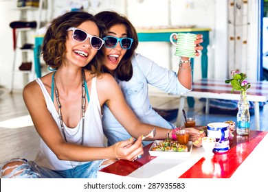 Two pretty best friend girls enjoy their lunch together in cute cafe, smiling speaking and gossip, bright clothes sunglasses, jewelry and accessorizes. portrait of women taking breakfast .
