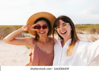 Zwei schöne Freunde Mädchen, die sich am Strand selbst machen, helle und helle Sommerfarben, schicke Boho-Kleiderhütten und Sonnenbrillen, trendiger Schmuck und natürliche Make-up, positive Freundschaftsvibes.