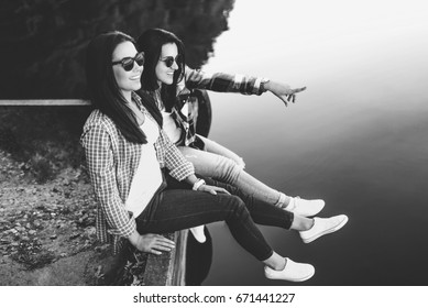 Two pretty brunette girls sitting on the pier near lake, black and white