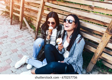 Two pretty brunette girls talking and eating ice cream outdoor