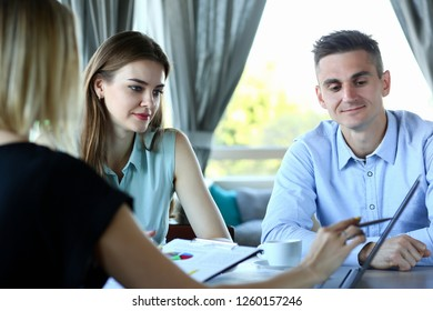 Two pretty businesswomen and businessman communicate in cafe room one points other in monitor with pen that is in her hand looks closely remote and listens about concept problem.