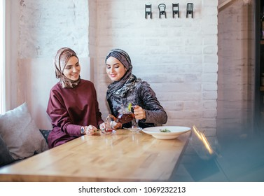 two Pretty caucasian muslim woman drinking tea in cafe