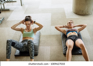 Two pretty Caucasian women doing exercises at gym.