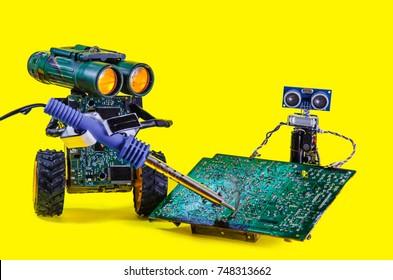 Two pretty cheerful robot repair printed circuit board
