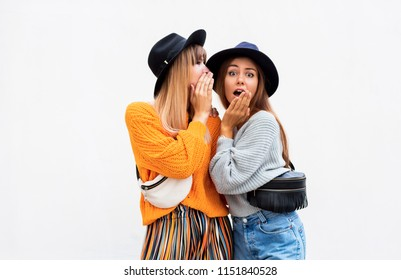 Two pretty cute   friends shares secrets, gossip. Surprise face,  emotions. Autumn outfit. knitted sweater. Black hat. Space for text.