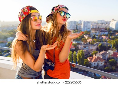 Two pretty fashion girls sending kiss and having fun, wearing bright swag caps and sunglasses, posing at the roof, positive nice emotions and mood, amazing view on city.
