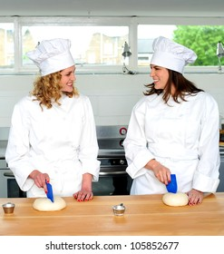 Two pretty female chefs looking at each other while kneading dough
