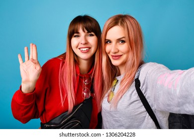 Two pretty funny women couple making selfie at studio , wearing hoodies and glasses, pastel pink trendy hairs, blue background, smiling and say hello.