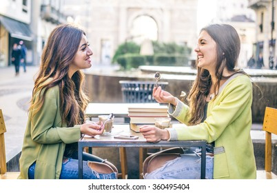 Two pretty girlfriends laughing while sitting in a bar outdoors - Students having pause and drinking cappuccino - Best friends talking and having fun