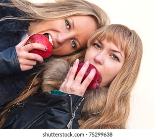 Two pretty girls eating apples