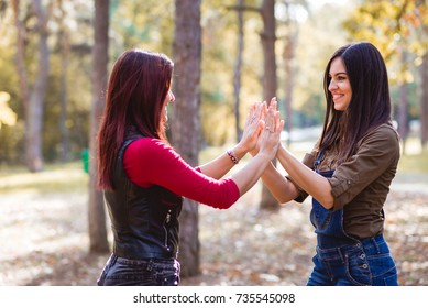 Two pretty girls having fun playing hand games in the park
