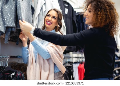 Two pretty girls looking at new collection of clothes in department store