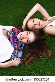 Two pretty girls lying on the fresh green grass
