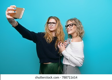 Two pretty girls are making selfie. Modern lifestyle. Studio shot over blue background.