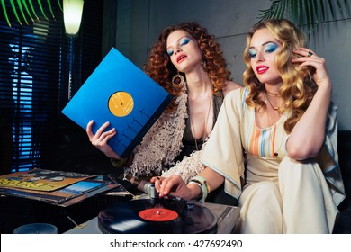 Two pretty girls models listening to vinyl records on the oldschool turntable. Furnishings, clothing and design in the style of the 70s