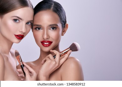 Two pretty girls with naked shoulders posing with make up brushes and smiling, wearing evening make up.
